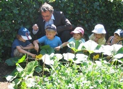 Einige Kinder des Kinder- und Familienzentrums zeigen Hans-Jürgen Serwe ihre Kürbispflanzen